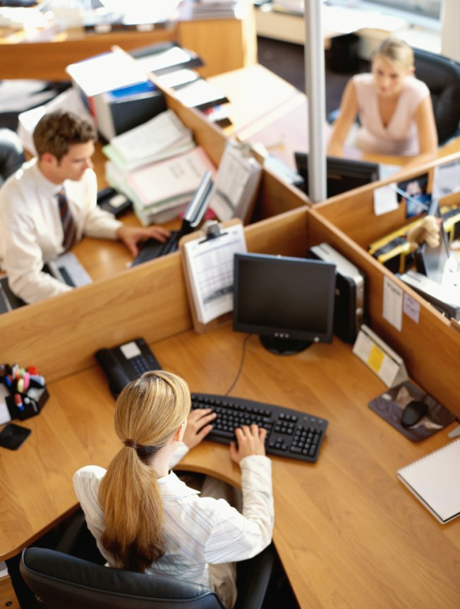 high angle view of a businessman and two businesswomen working in an office