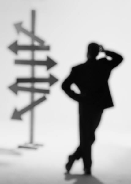 Business man looking at arrows pointing in different directions