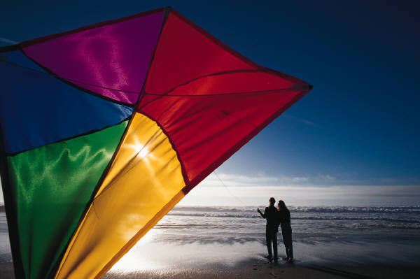 couple fly a kite together at the seaside