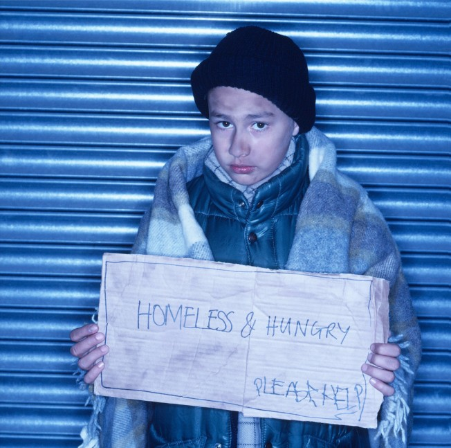 Homeless Young Boy Holding a Sign
