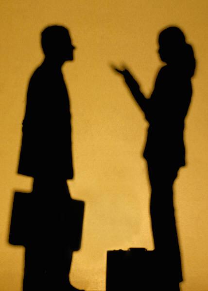 silhoutte of two business people talking