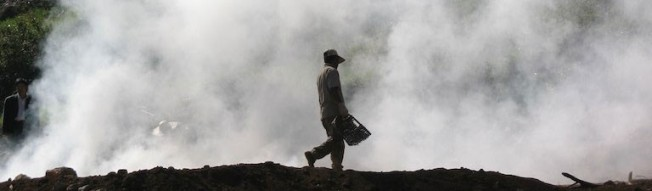 resilience - worker in Chile walks along charcoal field